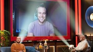 Un homme qui sourit et qui porte un chandail lilas. Il apparaît dans un écran.