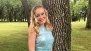 Une adolescente portant une robe bleu pose devant la caméra.