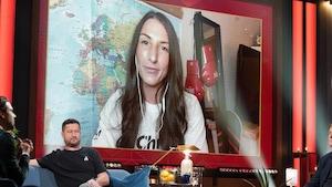 Une femme aux longs cheveux bruns. Elle apparaît sur un écran.