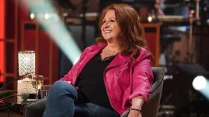 Une femme aux cheveux roux qui sourit. Elle porte une veste rose.