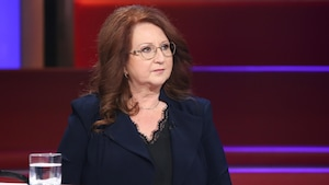 Une femme aux longs cheveux roux. Elle porte un veston bleu marine.