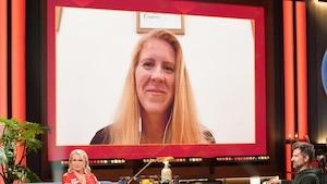 Une femme aux cheveux blonds. Elle apparaît sur un écran.