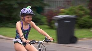 Une fillette fait du vélo dans une épreuve de triathlon.