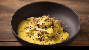 Un bol creux en terre cuite noir, rempli d'un curry de légumes, espuma de pomme de terre au safran et coco, cake aux pois chiches.