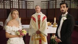 Devant l'autel à l'église, un prêtre se tient debout avec une homme et une femme en habits de mariage.