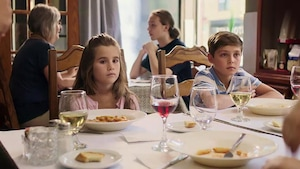Dans un restaurant, deux enfants sont assis côte à côte et ont un air grave.