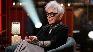 Un femme qui sourit. Elle porte des lunettes à grosses montures noires, un pantalon gris et une veste noire.