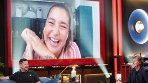 Une femme qui rit. Elle apparaît sur un écran.