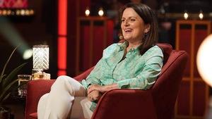 Une femme aux cheveux bruns qui sourit. Elle porte une chemise imprimée verte et un pantalon beige.