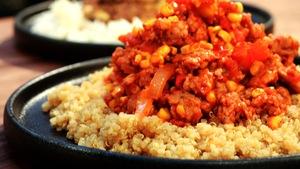 Un assiette avec un monticule de quinoa et le boeuf sur le dessus.