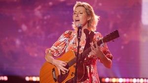 Une femme qui chante en s'accompagnant à la guitare.