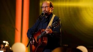 Un  homme qui chante en s'accompagnant à la guitare.