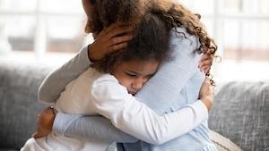 Une mère et sa fille assises sur un fauteuil se serrent dans leurs bras.