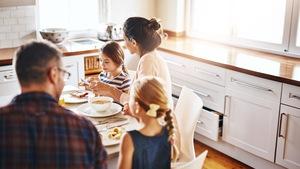 Des parents et leurs deux filles sont en train de déjeuner à table dans leur cuisine.