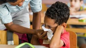 Un professeur donne un papier mouchoir à un enfant qui saigne du nez.