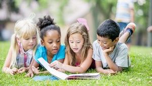 Quatre enfants allongés dans le gazon sont en train de lire un livre.