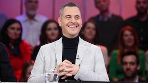 Un homme aux cheveux très courts et grisonnants. Il porte un chandail à col roulé noir et un veston gris pâle.