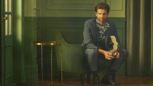 Jean-Philippe porte un habit. Le col de sa chemise est ouvert. Il tient une statuette dans ses mains.