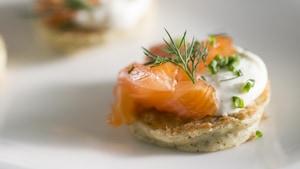 Blinis à l'algue surmontés d'un gravlax de saumon aux herbes salées, d'une crème aigrelette au citron et au poivre long et d'une branche d'aneth.