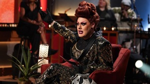 Une drag queen qui porte une perruque rousse et une robe dorée avec des imprimés.