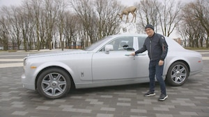 Michel Barrette est devant une voiture de collection grise.