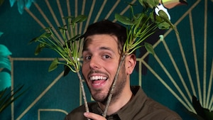 Il blague en tenant deux branches de verdure de chaque côté de sa tête.