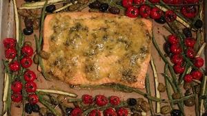 Le saumon est posé sur une plaque allant au four. Il est accompagné de haricots verts, d'asperges, de tomates cerises et d'olives.