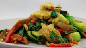 L'assiette est garnie de morceaux de porc et de légumes variés.
