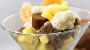 Il est servi dans une coupe avec des fruits.