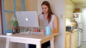 Une femme travaille avec un ordinateur portable sur une petite table devant sa cuisine.