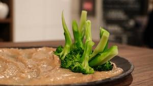 Assiette dans laquelle est déposée une trempette avec un bouquet de brocoli inversé.