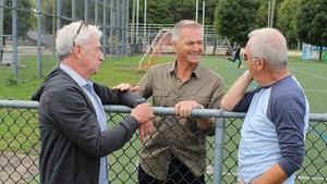 Accotés sur la clôture d'un terrain de soccer, Michel Barrette et Guy Mongrain écoutent les anecdotes de Dany Dubé.