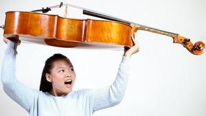 Jessica Tang tient son violoncelle au-dessus de sa tête.