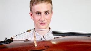 Le candidat Matej Hentosz tient son violoncelle sous son menton.