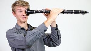 Victori Raphals-Kath regarde dans sa clarinette comme si c'était un télescope.