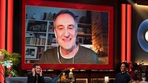 Un homme qui porte un chandail gris. Il apparaît sur un écran.