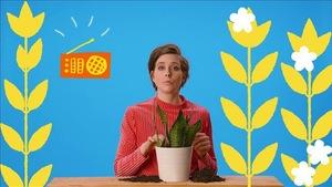 La comédienne est entourée de fleurs, elle explique comment mieux composter.