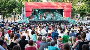 Une foule d'enfants et leurs parents sont assis dans un parc devant une scène de théâtre.