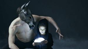 Un enfant ouvre un livre lumineux à côté d'un danseur portant un masque de cheval.