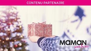Contenue partenaire Maman pour la vie : deux mains portent un cadeau vers un arbre de Noël en arrière-plan.