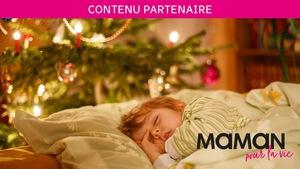 Contenu partenaire Maman pour la vie : un enfant dort à côté d'un sapin de Noël illuminé.