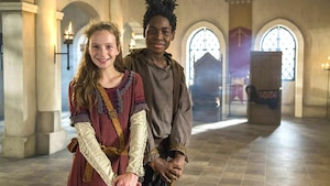 Valérie et Mehdi se tiennent debout avec leurs épées dans la salle du trône du château.