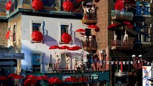 Des acrobates et des parapluies rouges sur la rue Saint-Denis, sur les balcons et sur les toits