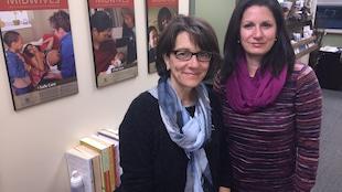 Paule Corneil et Kim Cloutier Holtz devant des affiches Ontario Midwives.
