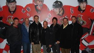 Sept hommes adultes sont alignés devant un mur décoré de la photo de joueurs de l'équipe de hockey des Sénateurs d'Ottawa.