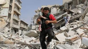 Un homme transporte un enfant dans ses bras tout en enjambant des ruines.