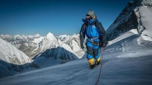 Un alpiniste américain sur le mont Everest avec un manteau bleu.