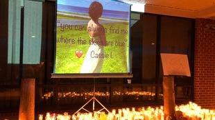 Des chandelles allumées sur une table devant une grande photographie de la jeune femme. Elle est près de la côte et regarde la mer.