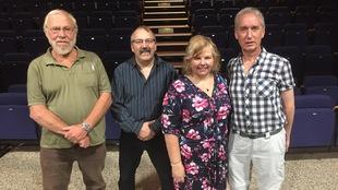 3 hommes et 1 femme sont debout devant les nouveaux sièges d'un théâtre rénové.