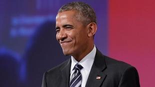 L'ancien président américain Barack Obama affiche un large sourire et des yeux rieurs.